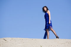 Blue dress. The young woman poses on the beach cold summer day Stock Photos