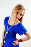 Blue dress. Young female fashion model wearing a blue dress standing against a white back drop Royalty Free Stock Photos