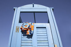 Blue dress cabin at the beach with a swimming suit hanging out Stock Photos