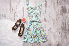 Blue dress in flowers and brown shoes. Wooden background, fashionable concept Stock Photos