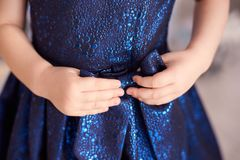 Blue dress. Great bow. Childrens hands. Horizontally. Blurred background. Light skin Stock Photo