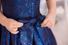Blue dress. Great bow. Childrens hands. Horizontally. Blurred light background Stock Photography