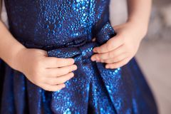 Blue dress. Great bow. Childrens hands. Horizontally. Blue dark dress. Great bow. Childrens hands. Horizontally. Light skin Royalty Free Stock Image