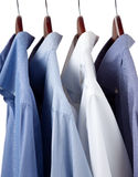 Blue dress shirts on wooden hangers Stock Photo