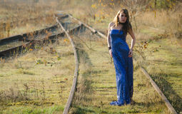 Blue dress on the tracks. Beautiful woman wearing a sparkling blue cocktail dress standing on overgrown train tracks Stock Photo