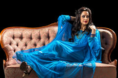 Blue dressed brunette on retro sofa Royalty Free Stock Images