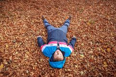 Man on the fallen leaves. Blue dressed man lying on the fallen orange leaves at autumn landscape royalty free stock image