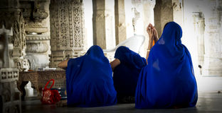 Blue dressed women praying. Royalty Free Stock Photography