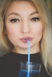Blue drink. Blond woman drinking blue drink using straw stock photos