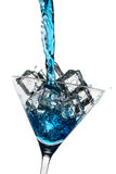 Blue drink poured into a glass with ice cubes Royalty Free Stock Photography