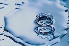 Blue drop. A blue drop of water over a mirror Stock Photos