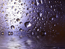 Blue droplet. Water droplets flooding out at bottom of the photo Royalty Free Stock Image