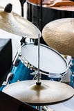 Blue drum and copper cymbals standing in street for musical perf Stock Image