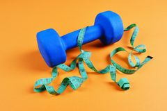 Blue dumbbell and meter on orange background royalty free stock photos