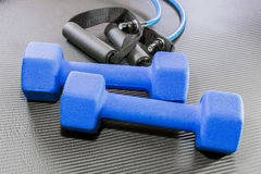 Blue dumbbell weights and resistance bands lying on a black yoga. Blue dumbbell weights and resistance bands lying on a black open yoga exercise mat Stock Photos