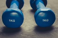 Blue dumbbells against a dark background/sports concept blue dumbbells against a dark background. Selective focus royalty free stock photography