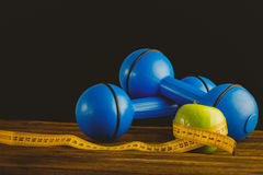 Blue dumbbells with green apple and measuring tape Stock Photo