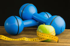 Blue dumbbells with green apple and measuring tape Stock Images