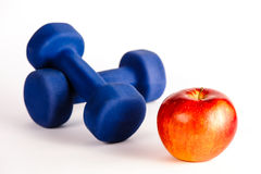 Blue dumbbells and red apple Royalty Free Stock Photos