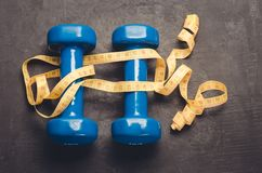 Blue dumbbells and yellow centimeter/ fitness concept with blue dumbbells and yellow centimeter on a dark background. Top view. Blue dumbbells and yellow stock photography