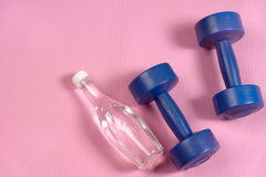 Blue dumbells on the pink yoga matt. And clear water bottle with copy space Stock Photo