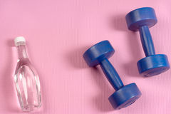 Blue dumbells on the pink yoga matt. And clear water bottle with copy space Royalty Free Stock Photography