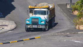 Blue Dump Truck Rolling with Full Load. A blue and white dump truck rolling down a hill with a full load of stone Stock Photo