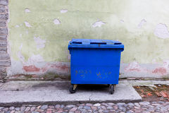 Blue dumpster against a bright green wall Royalty Free Stock Images