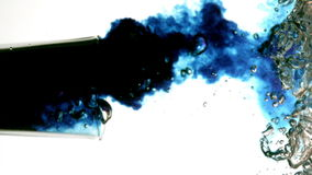 Blue dye moving in water on white background. In slow motion stock video