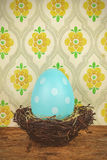 Blue dyed big easter egg in a bird nest on a wooden table stock images