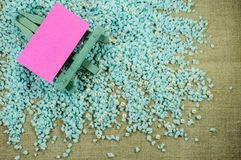 Blue easel with pink paper for inscriptions on the crumbled blue gravel. Stock Photo