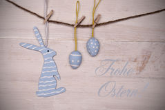 Blue Easter Bunny And Easter Eggs Hanging On Line With German Happy Easter. One Blue Easter Bunny With Stripes Hanging On A Line With Two Blue Easter Eggs Which Royalty Free Stock Images