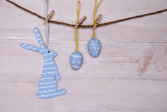 Blue Easter Bunny And Easter Eggs Hanging On Line. One Blue Easter Bunny With Stripes Hanging On A Line With Two Blue Easter Eggs Which Are Dotted And Striped On Stock Image