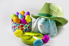 Blue Easter bunny rabbit with Green straw hat and gift box  with easter colorful  eggs. Picture of a Blue Easter bunny rabbit with Green straw hat and gift box Royalty Free Stock Photography