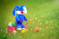 Blue Easter Bunny Riding a Tricycle Carrying Easter Eggs Stock Image