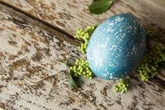 Blue Easter egg, decorated with flowers, on wooden board. Royalty Free Stock Photos