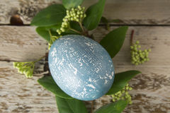 Blue Easter egg, decorated with flowers, on wooden board. Stock Photos