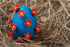 Blue easter egg decorated with red flowers Royalty Free Stock Photo