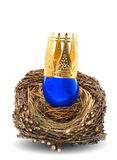 Blue easter egg with golden crown decoration. In wooden nest isolated on white background Royalty Free Stock Photo