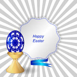 Blue easter egg with ornament on a support, a tag with ribbon. Stock Photos