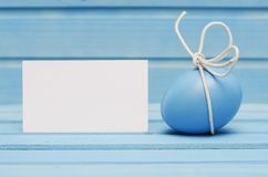 Blue Easter egg with white bow on blue wooden background with blank card Stock Image