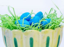 Blue Easter Eggs on Lime Green Nest in yellow bowl. Blue speckled candy easter eggs in a nest of lime green straw sitting in a pretty yellow and green bowl royalty free stock photo