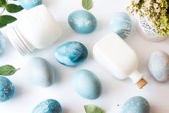 Blue Easter eggs, white bottles and flowers Stock Images