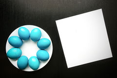 Blue easter eggs on a white plate, on a black wooden background. Royalty Free Stock Photos
