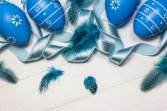 Blue Easter eggs on white wooden background stock photography