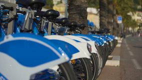 Blue eco-bicycles standing in row on street, bikes for hire, urban transport stock footage