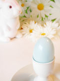 Blue egg in egg cup. White easter bunny looking on at blue easter egg in white egg cup Stock Image