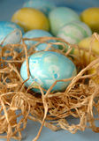 Blue Egg In Raffia nest. A blue Easter egg in a little raffia nest with more eggs behind Stock Images