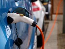 Blue Electric Car Charging. Close-up of a electric car plugged to the filling point,charging the battery Stock Photo