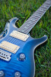 Blue electric guitar. Lying on green grass Royalty Free Stock Photography